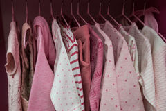 A lot of white children`s clothes on hangers. Children`s wardrobe with clothes.  Stock Photo