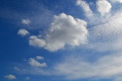 A lot of white clouds of different types: cumulus, cirrus, layered high in blue sky stock photography