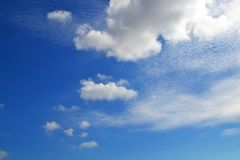 A lot of white clouds of different types: cumulus, cirrus, layered high in blue sky stock photo