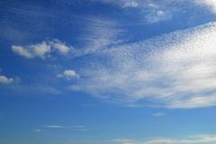 A lot of white clouds of different types: cumulus, cirrus, layered high in blue sky stock images