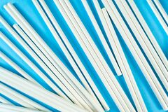 A lot of white paper tubes are scattered randomly on a blue background. The view cocktail tube texture. Zero waste