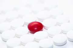 White pills with a red pill. Lot of white pills with one single red pill Royalty Free Stock Images