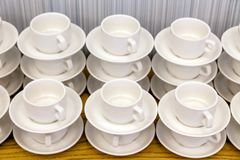 Lot of white porcelain tea pairs in piles in a straight line. Co stock images