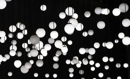 A lot of white round lamps on a black background royalty free stock images