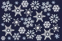 A lot of white snowflake painted with paint through a stencil on a dark blue background. A lot of white snowflake painted with paint through a stencil on a dark stock photography