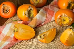 Lot of whole persimmons, chopped pieces of fruit, and napkin Royalty Free Stock Photo