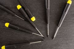 Work tool item on grey stone. Lot of whole screwdrivers with a yellow black plastic handle work item flatlay on grey stone royalty free stock image