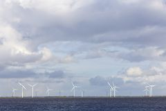 Lot of wind turbines on dutch island of flevoland behind water. Lot of wind turbines on dutch island of flevoland seen from eempolder in noord-holland Royalty Free Stock Image