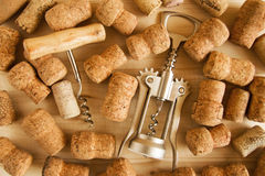A lot of wine corks and two corkscrews on the wooden background. royalty free stock photos