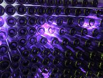 lot of wine glass bottles on a wall and indirect light in purple color, background and texture royalty free stock photo