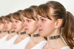A lot of women in a row with barcode - genetic clone concept. A lot of woman in a row with barcode on neck - genetic clone concept stock photo