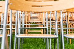 Wooden chairs stand outside in the park in the rain. Empty auditorium, green grass, waterdrops, closeup. Lot of wooden chairs stand outside in the park in the royalty free stock images