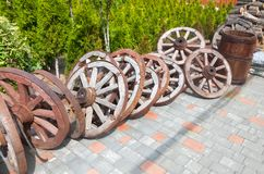 A lot of wooden wheels from old carts in disorder, piled in the. A lot of wooden wheels from old carts and cask in disorder, piled in the yard Stock Image
