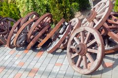 A lot of wheels from old carts in disorder, piled in the yard. A lot of wooden wheels from old carts in disorder, piled in the yard Stock Images