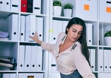 Young woman taking folder with documents from shelf in archive. A lot of work in the accounting company. royalty free stock image