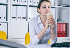 Lot of work wait for dreaming woman with coffe in hans. Dream of a vacation. Lot of work wait for dreaming woman with coffe in hans. Huge pile of document Royalty Free Stock Photos