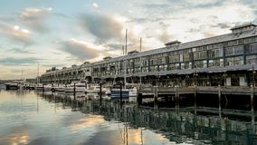 Yachts and small motor boats moor along the Woolloomooloo wharf in Sydney harbour, Sydney Australia royalty free stock photo