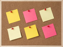 Lot a yellow, pink stickry note on wooden frame cork board.  Royalty Free Stock Image