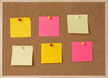 Lot a yellow, pink stickry note on wooden frame cork board.  Royalty Free Stock Images
