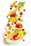 Lote das frutas diferentes que caem no leite Fotografia de Stock