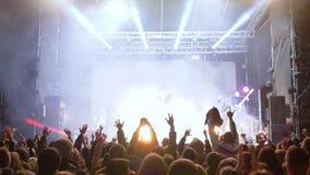 Lote das mãos de ondulação dos povos acima durante o desempenho do músico da rocha na cena iluminada no fumo video estoque