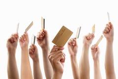 Lote das mãos que prendem o cartão de crédito do ouro Fotografia de Stock Royalty Free