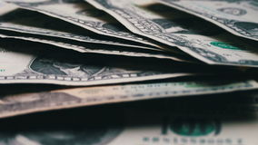 Lote das notas de dólar pequenas que balançam no vento na tabela com um fim branco do macro do fundo acima filme