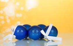 Lote de brinquedo-bolas azuis do Natal com fita branca, no fundo amarelo Imagens de Stock Royalty Free