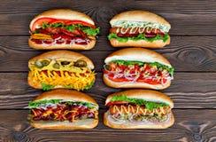 Lote de cachorros quentes deliciosos grandes com molho e vegetais no fundo de madeira Imagens de Stock Royalty Free