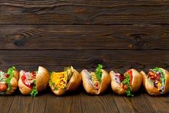 Lote de cachorros quentes deliciosos grandes com molho e vegetais no fundo de madeira Imagem de Stock Royalty Free