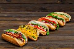 Lote de cachorros quentes deliciosos grandes com molho e vegetais no fundo de madeira Fotos de Stock