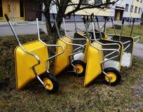 Lote de carrinhos de mão amarelos novos vazios do jardim na jarda Fotografia de Stock Royalty Free