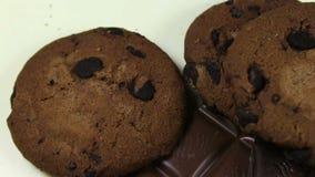 Lote de cookies do bolo da microplaqueta com inclinação do close-up do chocolate e de partes de leite e de chocolate escuro filme