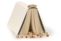 Lote - mensagem soletrada em letras de madeira sobre um livro da história Imagens de Stock Royalty Free