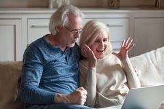 Lotería que gana envejecida emocionada de los pares en línea en el ordenador portátil fotografía de archivo libre de regalías