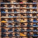 Lotes das sapatilhas diferentes das sapatas, botas, plimsolls na mostra no mercado Imagem do esporte que segue botas em uma loja- imagem de stock