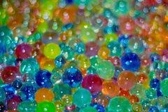 Lotes de bolas de vidro coloridas de tamanhos diferentes como um fundo com bokeh imagem de stock