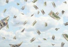Lotes de cem dólares de cédulas que caem do céu nebuloso azul Fotos de Stock Royalty Free
