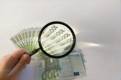 Lotes de cem euro- contas e lupa Imagem de Stock Royalty Free
