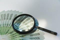 Lotes de cem euro- contas e lupa Fotografia de Stock Royalty Free