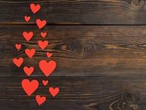 Lotes de corações de papel vermelhos em um de madeira resistido rústico do marrom escuro Foto de Stock