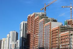 Lotes do canteiro de obras da torre com guindastes e da construção com fundo do céu azul foto de stock royalty free