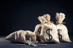 Sacos completamente do dinheiro em um fundo escuro Fotografia de Stock Royalty Free
