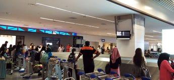 Lotes dos povos que obtêm a bagagem no aeroporto fotografia de stock