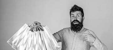 Lotes levando do noivo dos sacos de compras e de apontar em sacos O homem com barba leva o grupo dos sacos de compras, cinzento fotos de stock royalty free