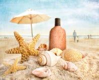 Lotion et seashells de bronzage sur la plage images libres de droits