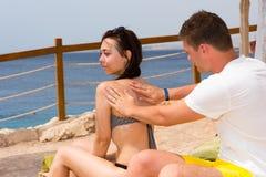 Lotion masculine de protection solaire de frottage sur le dos de la femelle tout en détendant Photo libre de droits