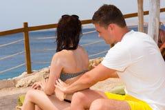 Lotion masculine de protection solaire de frottage sur le dos de la femme tout en détendant Photo stock