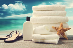 Lotion, towels and sandals with ocean scene Royalty Free Stock Image