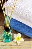Lotniczego freshener aromatyczni kije i sterta czyści ręczniki na starym drewnianym stole w domu Domowej roboty trzcinowy dyfuzor zdjęcia stock